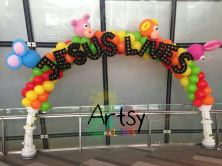 "Rainbow balloon arch with columns at the side and ""JESUS LIVES"" advance balloon alphabets"