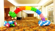 Rainbow balloon arch with monkeys on a tree