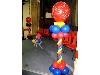 Bright spiral red, yellow and blue balloon columns with large red starry balloon on the top