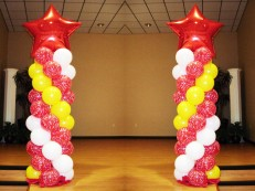 Red spiral starry balloons with white & yellow balloons and a large red foil balloon on the top