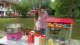 couple handling popcorn and candy floss machine