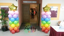 Rainbow balloon columns with a gold foil star on the top
