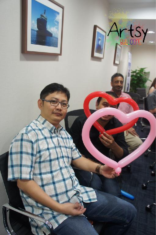 Guy holding balloon heart sculpture