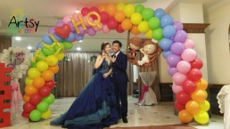 Balloon wedding couple on rainbow balloon arch
