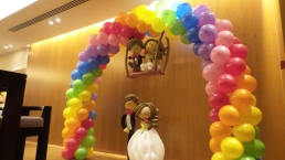 Full rainbow balloon arch with wedding couple on swing