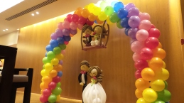 Full rainbow balloon arch with wedding couple on swing