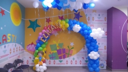 rainbow balloon arch with sky and clouds
