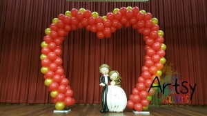 heart shaped arch with life sized wedding couple balloon sculpture