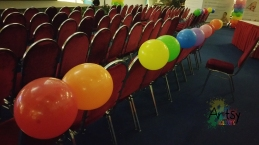 Rainbow balloons tied to chair