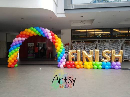 Rainbow balloon arch with a loud FINISH foil balloons at the side!