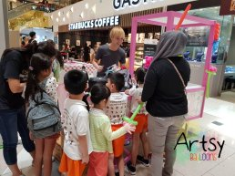 Ouji doing balloon sculpting for kids four shopping mall events