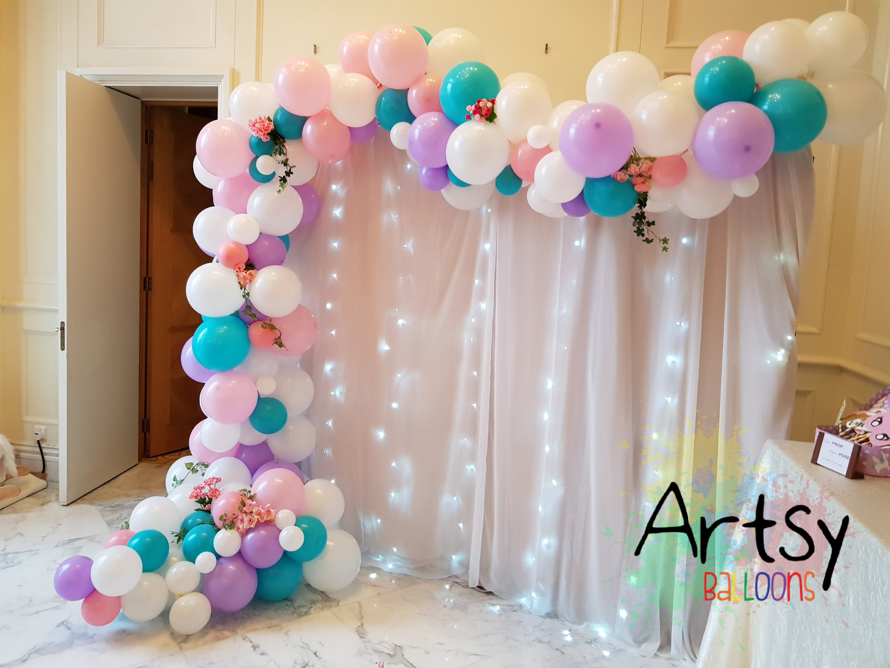 Organic balloon decorations with cloth backdrop and LED lights