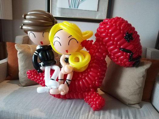 Couple sitting on dinosaur balloon sculpture
